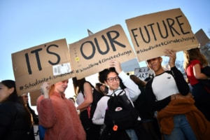 Young demonstrators hold placards as they attend a climate change protest organised by